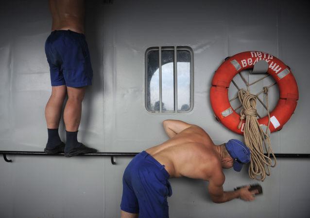 بحارة  يعملون على تنظيف الطراد بطرس الأكبر (بيوتر فيليكي) النووي، قبل الوصول إلى قاعدة أسطول المحيط الهادئ في فوكينو في خليج ستريلوك