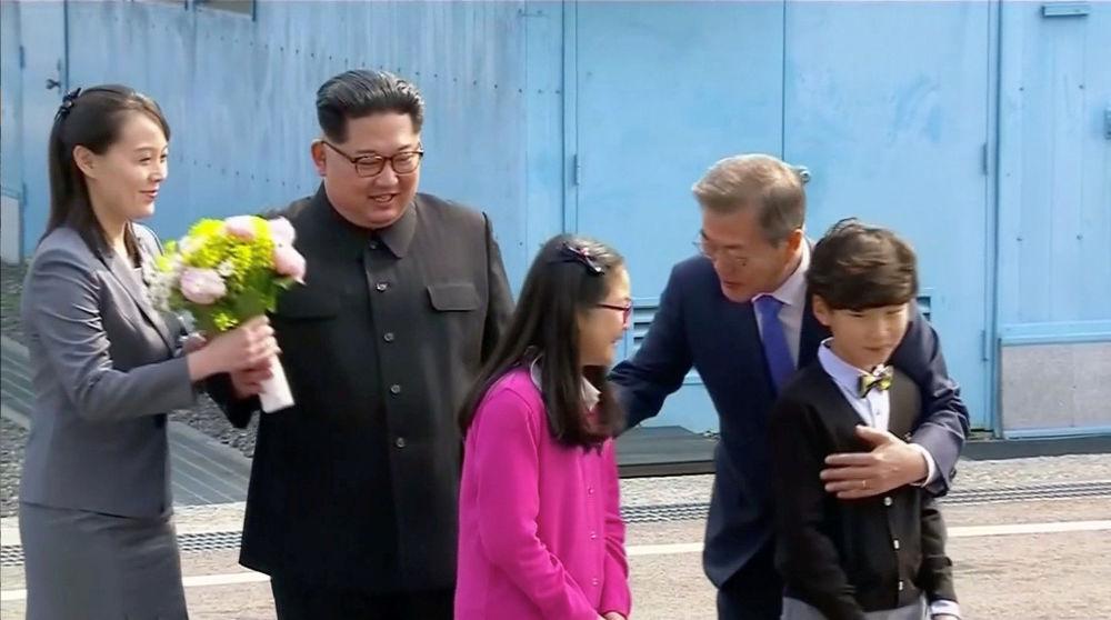 الزعيم الكوري الشمالي كيم جونغ أون وشقيقته كيم يو جونغ إلى جانب الرئيس الكوري الجنوبي مون جاي-إن بعد أن أهدى الأخير باقة من الأزهار لها، وذلك قبل اللتوجه إلى القمة الكورية المشتركة في قرية الهدنة في بانمونجوم، كوريا الجنوبية 27 أبريل/ نيسان 2018