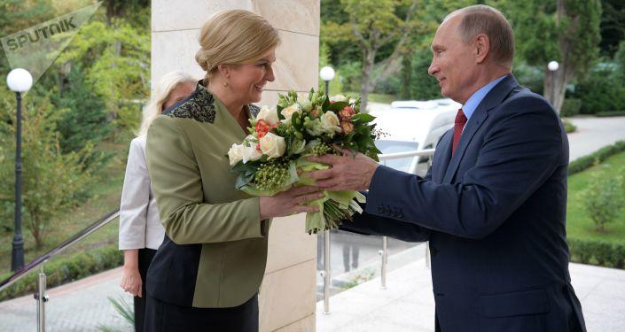 الرئيس الروسي فلاديمير بوتين يهدي باقة من الأزهار لرئيسة لرئيسة جمهورية كرواتيا كوليندا غرابر-كيتاروفيتش لدى وصولها إلى سوتشي، 2018