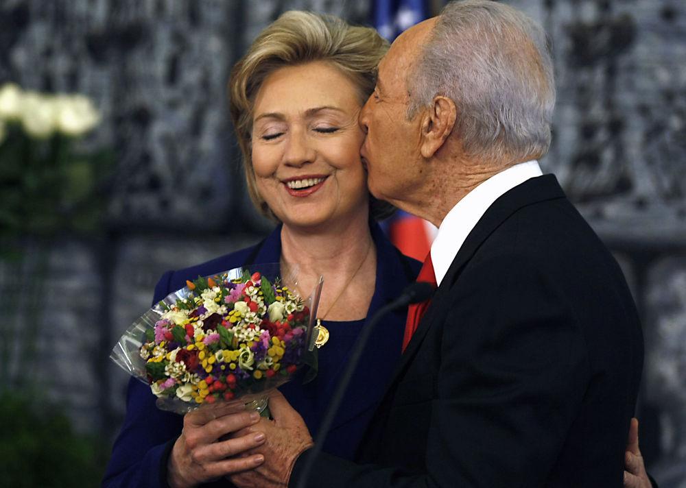 الرئيس الإسرائيلي شمعون بيريز يهدي باقة من الأزهار لوزيرة الخارجية الأمريكية هيلاري كلينتون في نهاية مؤتمر صحفي بعد اجتماعهما في القدس، 3 مارس/ آذار 2009