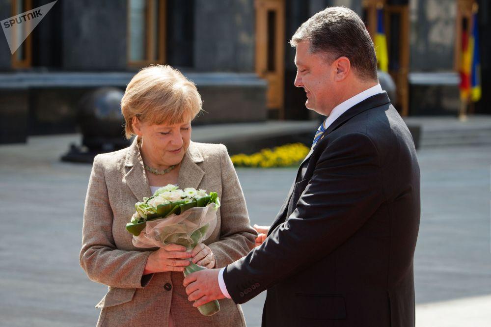 الرئيس الأوكراني بيوتر بوروشينكو يهدي باقة من الأزهار لمستشارة ألمانيا أنجيلا ميركل خلال زيارتها إلى كييف، أوكرانيا 2014