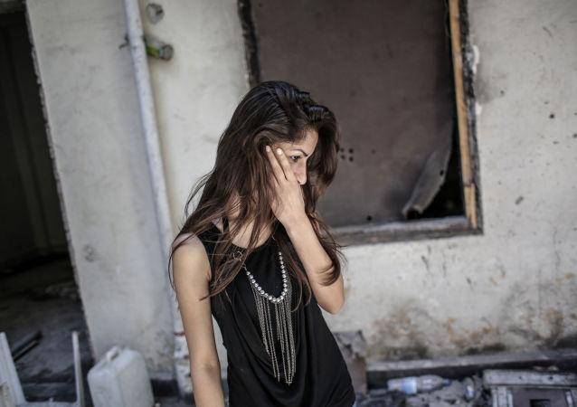 فتاة تتفحص منزلها في وسط الركام في مدنية حمص، بعد أن تركته خلال العمليات العسكرية