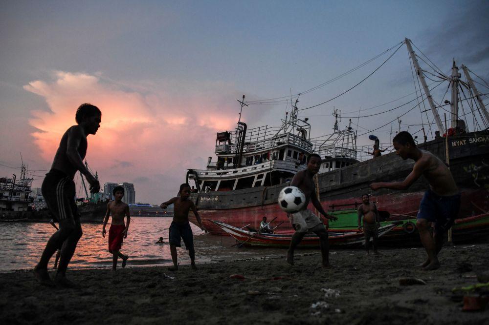 شباب ميانمار يلعبون كرة القدم على ضفة نهر يانغون في يانغون 21 مايو/ أيار 2018