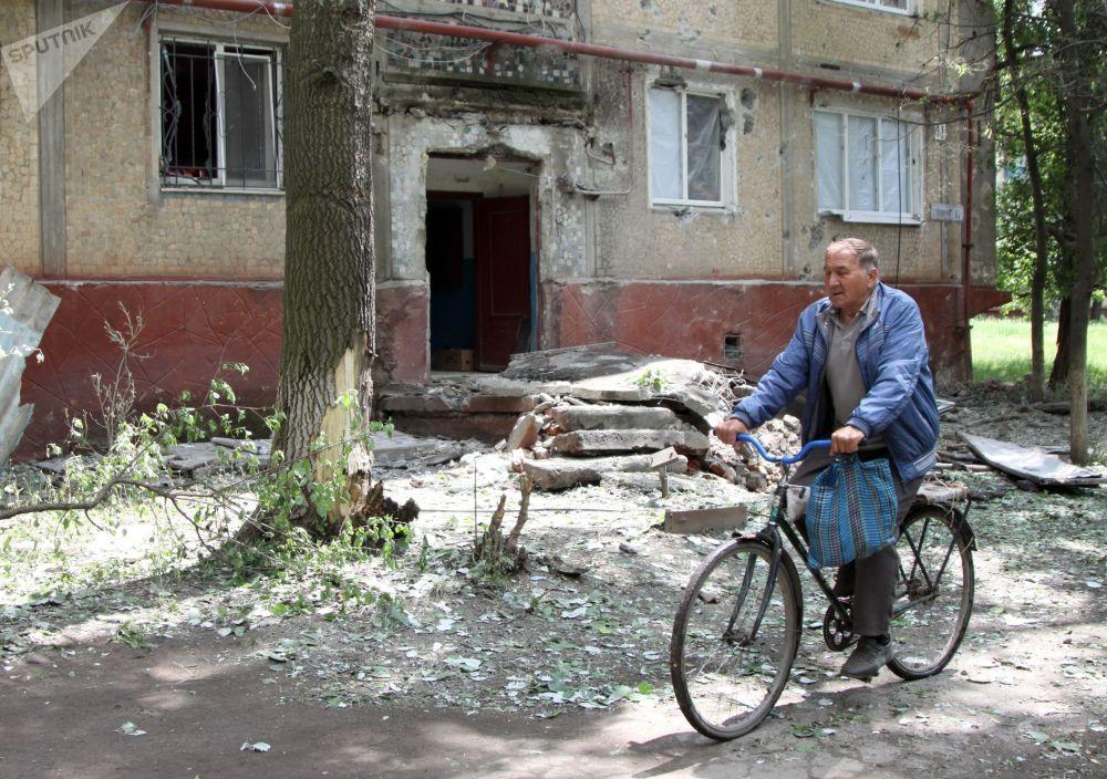 رجل يركب دراجة هوائية بجوار منزله في بلدة غورلوفكا في دونيتسك