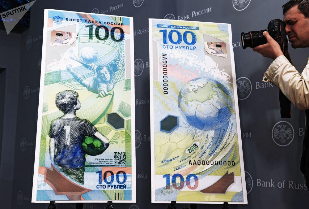 مصور صحفي يلتقط صورة لمجسم ورقة نقدية بلاستيكية من قيمة مائة روبل في ذكرى استضافة روسيا لمونديال كأس العالم لكرة القدم للمرة الأولى في تاريخها