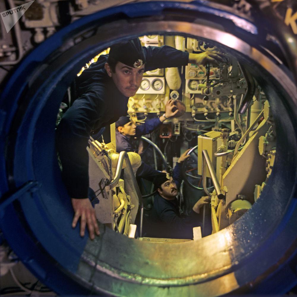 قائد الطاقم ألكسندر كولوميكو، وكبير المتخصصين يوري شوستوف، والبحار الكهربائي ألكسندر دراجكو داخل غواصة نووية تابعة للأسطول الشمالي السوفيتي