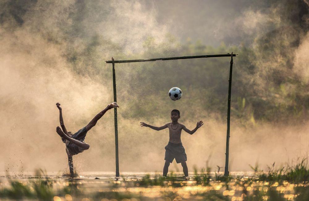 صبيان آسيون يلعبون كرة القدم في الريف