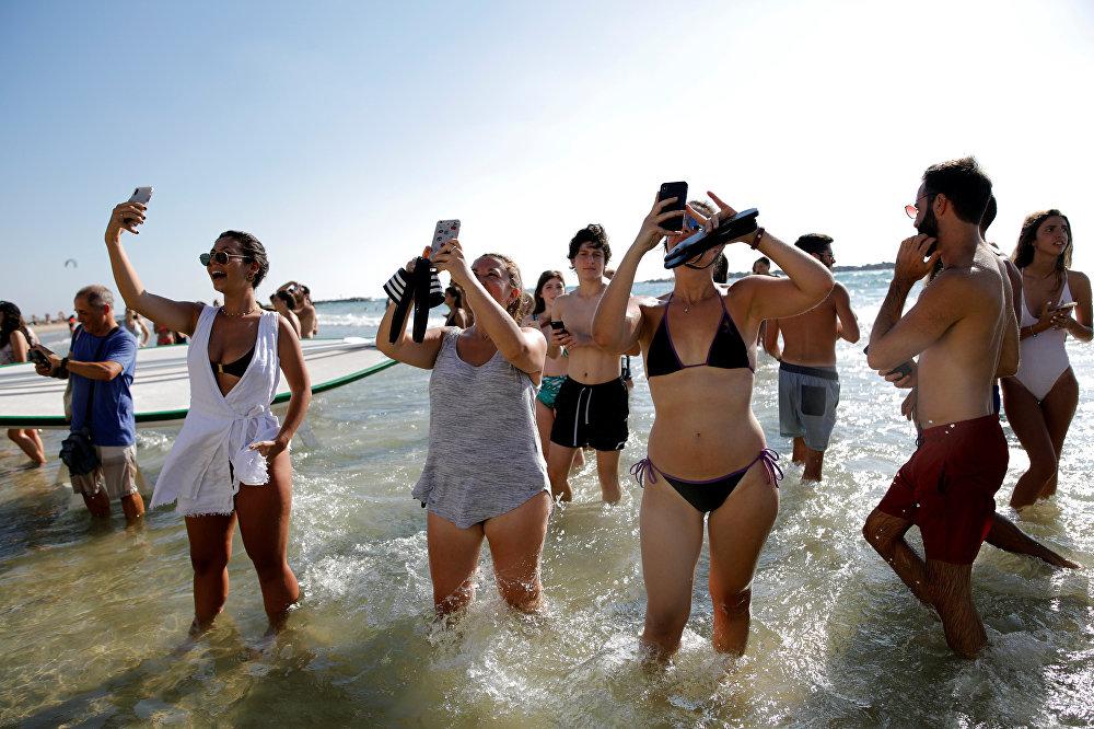 المصطافون على الشاطئ يلتقطون صور لنجل ولي عهد بريطانيا الأمير وليام خلال أول زيارة ملكية له لإسرائيل، 26 يونيو/حزيران 2018
