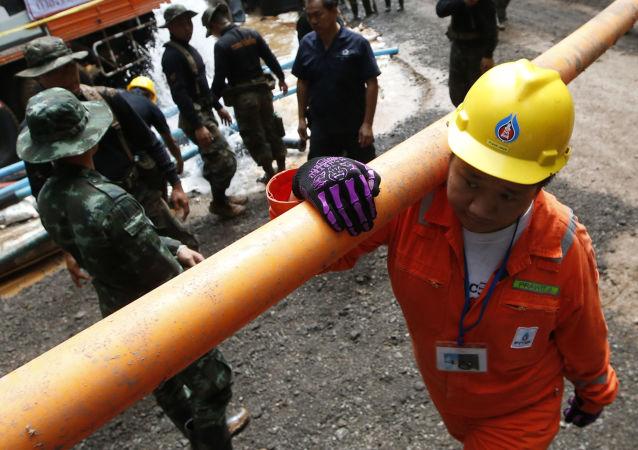 عمال الإنقاذ مع أنبوب مياه أثناء عملية إنقاذ بالقرب من الكهف في تايلاند
