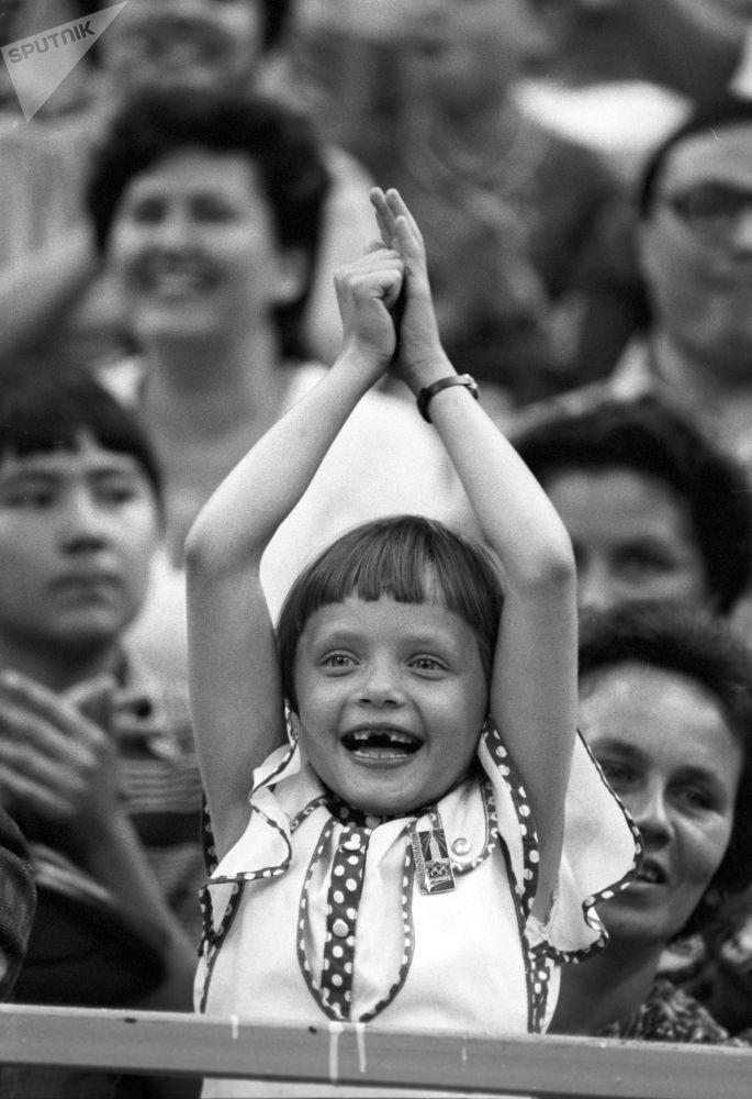 مشجعة صغيرة خلال تجشيعها لمنتخب الاتحاد السوفيتي، خلال مباراة كرة السلة بين الاتحاد السوفيتي وجمهورية يوغوسلافيا الاتحادية الاشتراكية (آنذاك)، في الألعاب الأولمبي الصيفية الـ 22 (19 يوليو - 3 أغسطس)، 1980