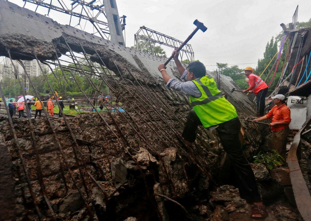 عمال الإنقاذ والسكك الحديدية يعملون في موقع الجسر الذي انهار فوق خطوط السكك الحديدية بعد هطول أمطار غزيرة في مومباي بالهند في 3 يوليو/ تموز 2018
