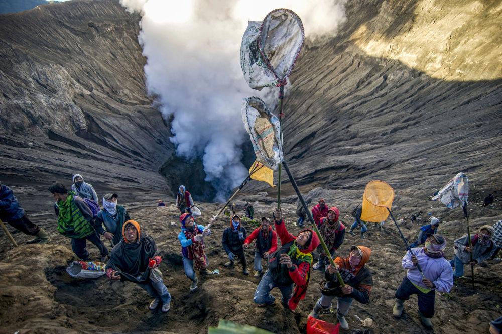 أشخاص يستعدون للإمساك بالقرابين اتي قدموها للتضحية، كنوع من مهرجان يادنيا كاسادا (Yadnya Kasada)، في بركان برومو مقاطعة جافا الشرقية، 30 يونيو/ حزيران 2018