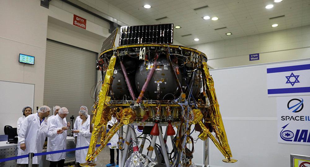 علماء إسرائيليون يقفون إلى جانب مركبة فضائية غير مأهولة تستعد للسفر إلى القمر