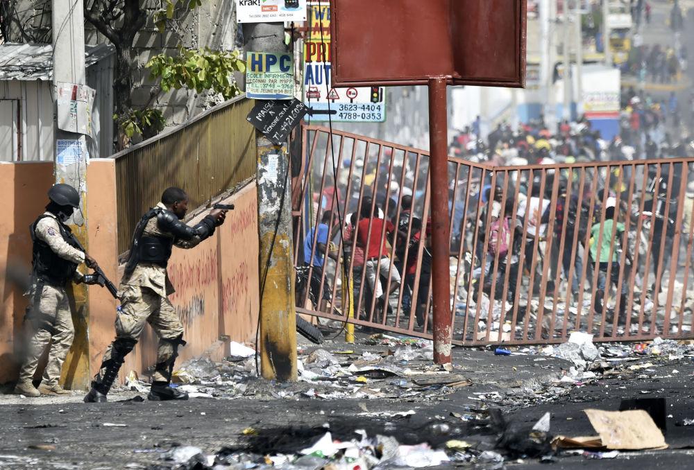 أحد أفراد الشرطة الهايتيّة يوجه مسدسه نحو الناس لتفادي النهب في المحلات التجارية في ديلماس، وهي بلدية قرب بورت-أو-برنس، خلال احتجاجات ضد ارتفاع أسعار الوقود، في 8 يوليو/ تموز 2018