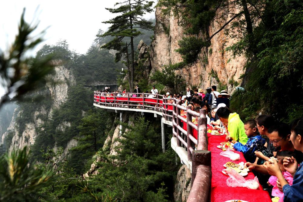 السياح خلال مأدبة طعام أقيمت على حافة جرف جبل لاوجون، على ارتفاع 2000 متر، في لويانغ بمقاطعة خنان بوسط الصين