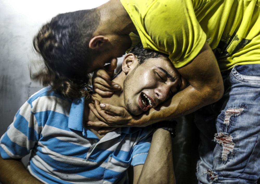 شباب فلسطينيون يبكون شابين قتلا في غارة جوية إسرائيلية في مدينة غزة، قطاع غزة، فلسطين 14 يوليو/ تموز 2018