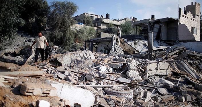 رجل فلسطيني يتفقد موقعا تابعا لـ حماس بعد القصف الجوي الإسرائيلي في منطقة المغراقة، ضواحي مدينة غزة، قطاع غزة، 9 أغسطس/ آب 2018