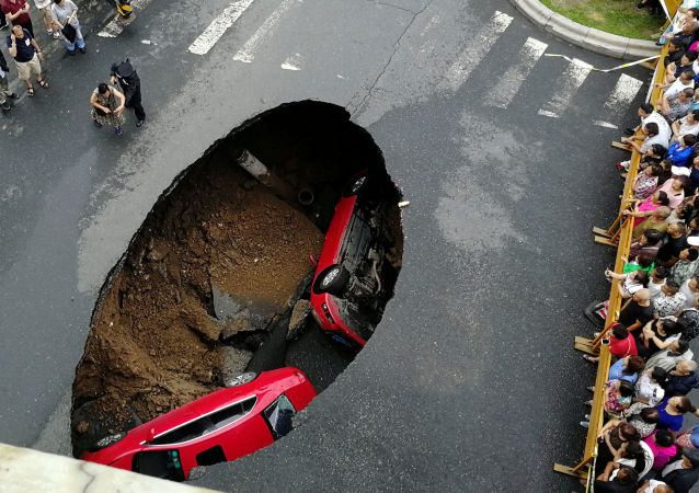 أشخاص يتجمعون حول حفرة سقطت فيها سياراتان وسط شارع في مدينة هاربين، الصين 4 أغسطس/ آب 2018