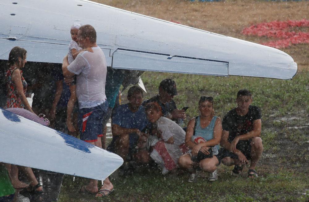 جمهور يختبئ تحت جناح طائرة أثناء هطول أمطار غزيرة في مسابقة أفيادارتس في إطار الألعاب العسكرية الدولية أرمي -2018  (الجيش - 2018) في منطقة ريازان الروسية 4 أغسطس / آب 2018