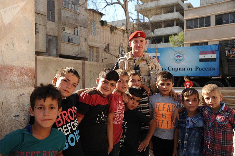 أطفال سوريون يلتقطون صورة جماعية مع عسكري روسي