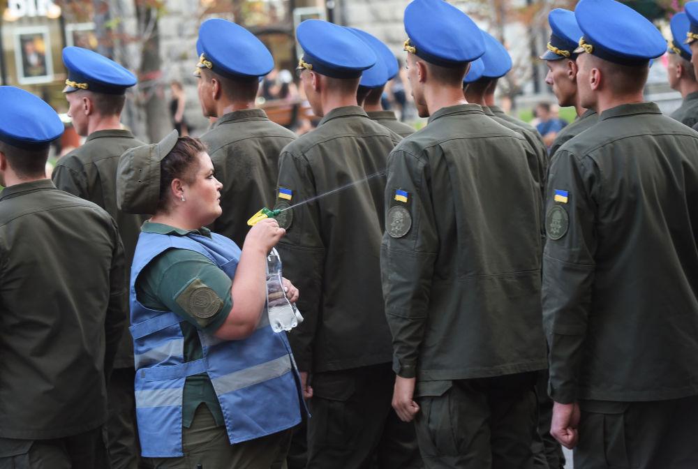 ممرضة عسكرية ترش المياه على الجنود المشاركين في بروفة العرض العسكري بمناسبة يوم الاستقلال، وذلك لتخفيف الجو الحار عليهم، في كييف، أوكرانيا 20 أغسطس/ آب 2018