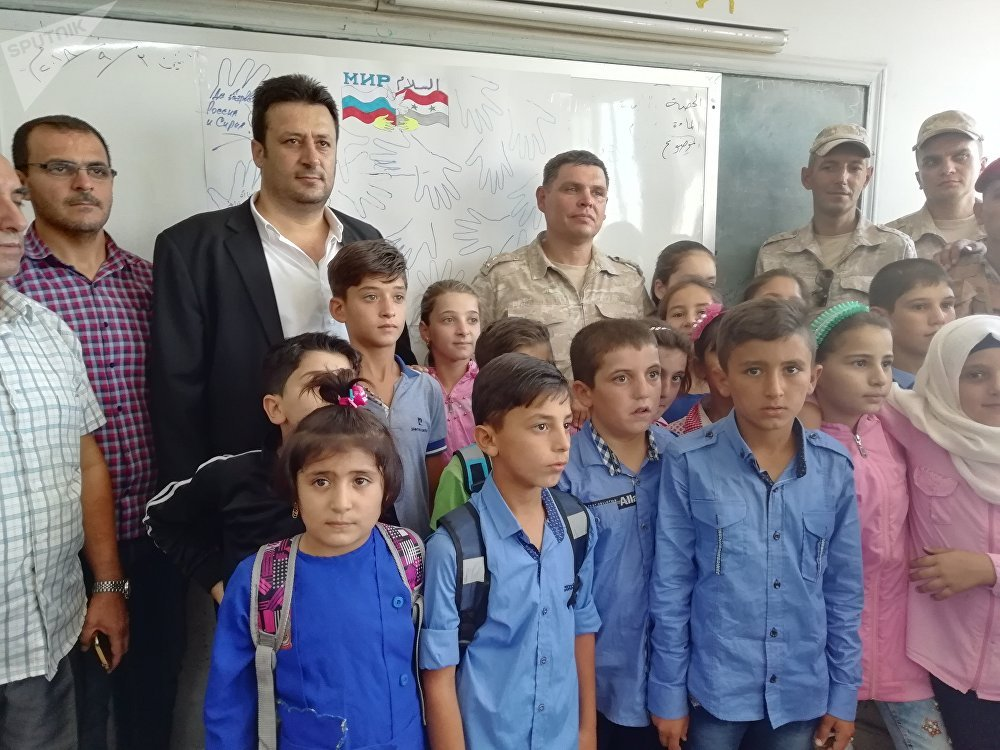 جنرال روسي وضباطه يشاركون أطفال قمحانة السورية يومهم الدراسي الأول