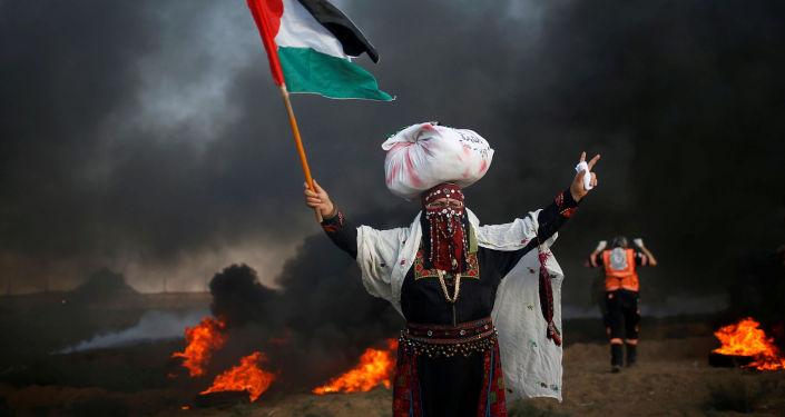 امرأة تحمل علم فلسطين خلال احتجاجات تدعو لرفع الحصار الإسرائيلي عن قطاع غزة، والمطالبة بحق العودة، على الحدود بين القطاع وإسرائيل، شرق مدينة غزة، 14 سبتمبر/ أيلول 2018