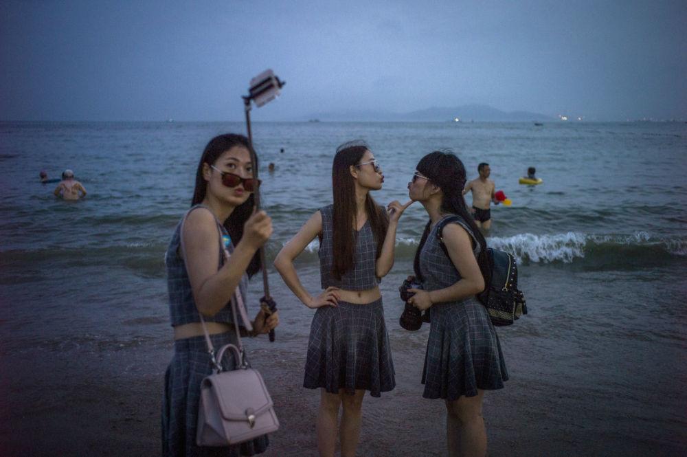 فتيات يلتقطن صور سيلفي على شاطئ بمدينة كينجداو، الصين