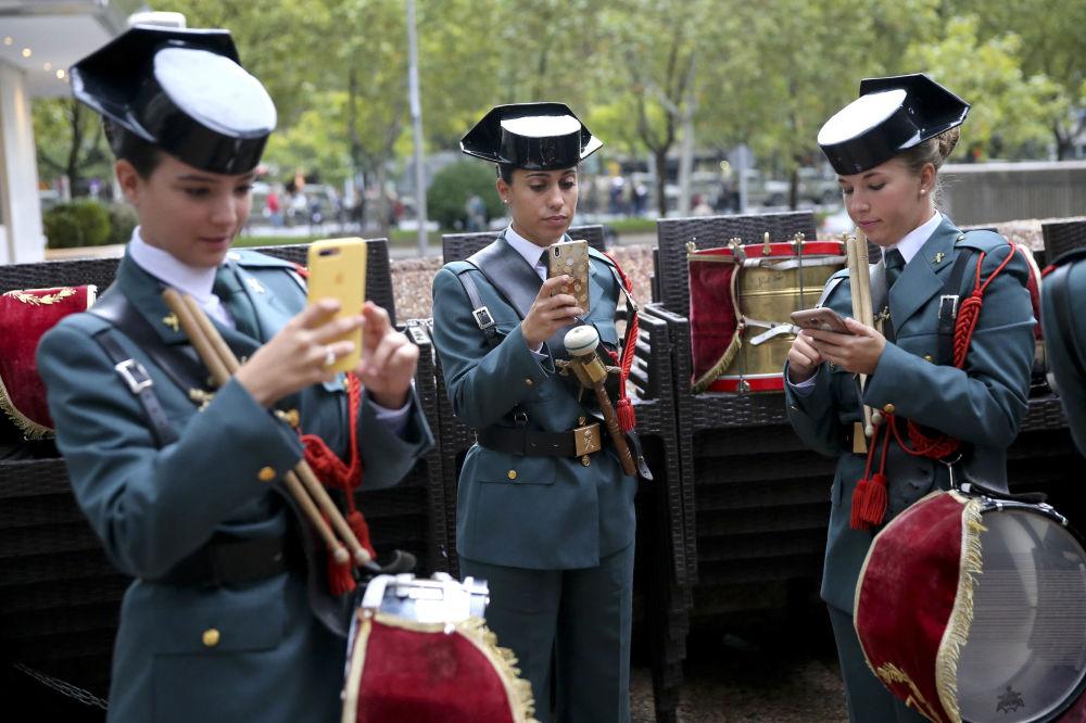 ضابطات حرس المدنية النسائية يتفقدن هواتفهن المحمولة، وفي انتظار بدء العرض العسكري بمناسبة الاحتفال باليوم الوطني في مدريد، إسبانيا، 12 أكتوبر/ تشرين الأول 2018