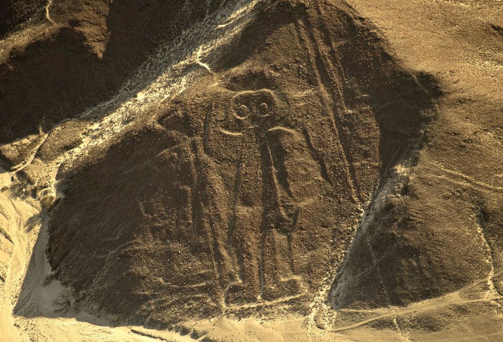 منظر جوي للجغرافيا المجسّمة والمعروفة باسم رائد الفضاء (بطول 30 متراً) في خطوط نازكا (نقوش جيولوجية قديمة جيوغليف)، على بعد 435 كم جنوب ليما في بيرو، في 11 ديسمبر/ كانون الأول 2014. لا يمكن رؤية الشكل إلا من فوق التلال المحيطة أو من الطائرات. لا يزال الغرض من وجود خطوط نازكا مبهما. طبقاً لبعض العلماء، فإن شعب نازكا هم من عملها ليراهم آلهتهم من السماء. وتغطي مساحة خطوط نازكا حوالي 500 كيلومتر مربع.