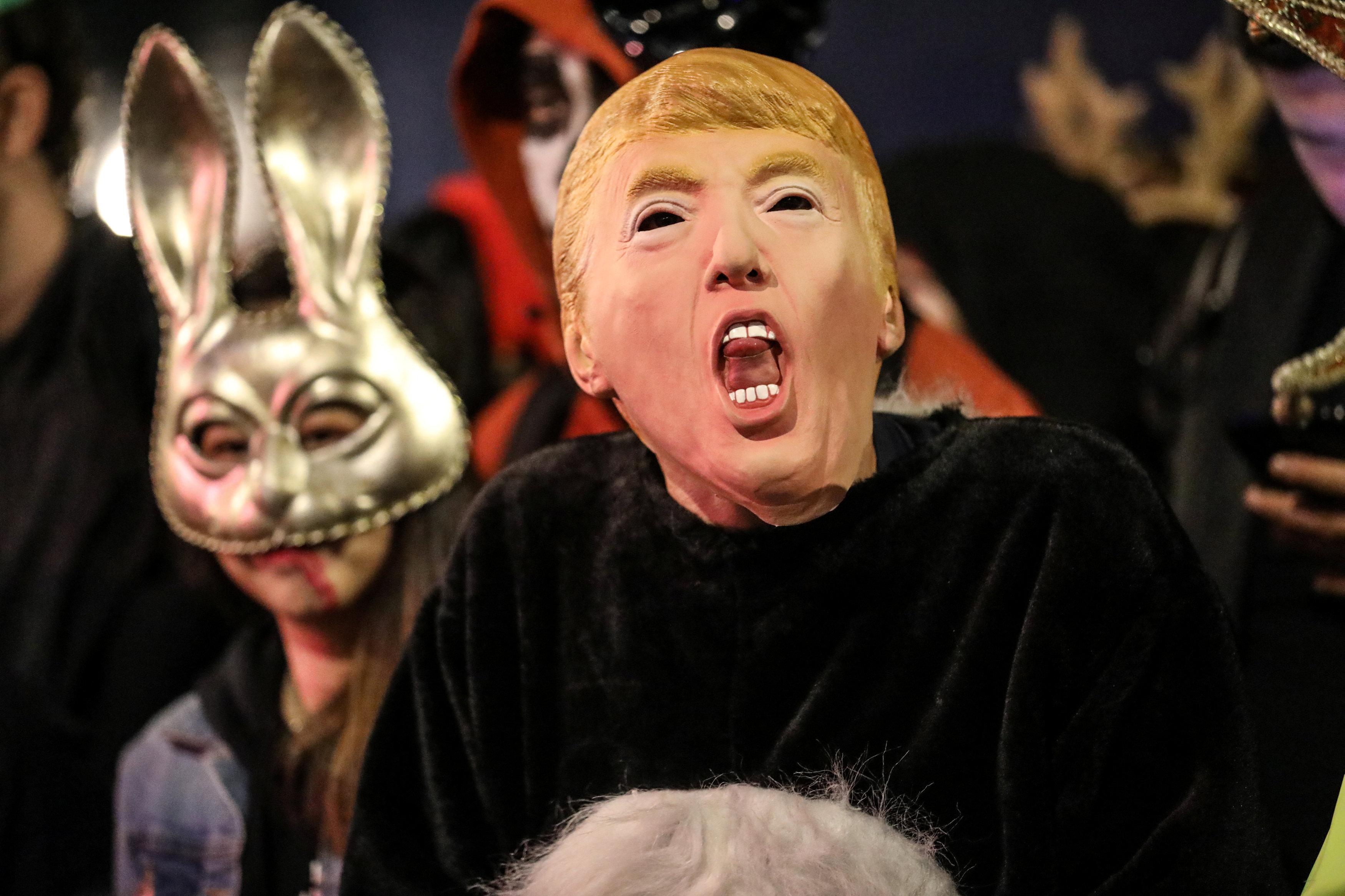 مشاركون في إحتفالات الهالوين في أمريكا يرتدون قناع الرئيس الأمريكي دونالد ترامب