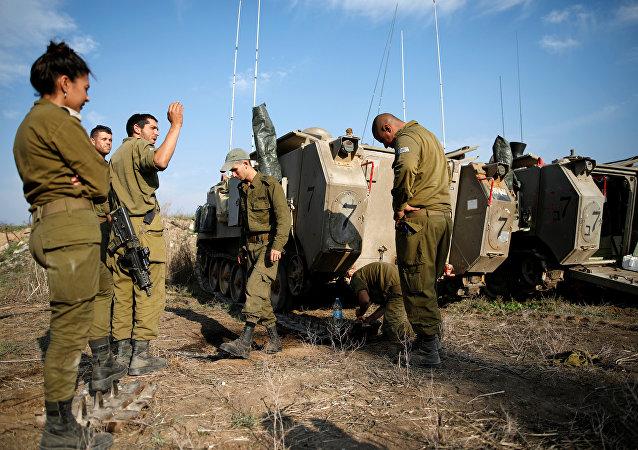جنود إسرائيليون يقفون بالقرب من حاملات الجند المدرعة (APC) في حقل في جنوب إسرائيل ، بالقرب من الحدود مع غزة
