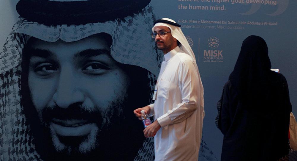 أحد المشاركين يسير بجوار صورة ولي العهد السعودي الأمير محمد بن سلمان خلال منتدى مسك العالمي في الرياض