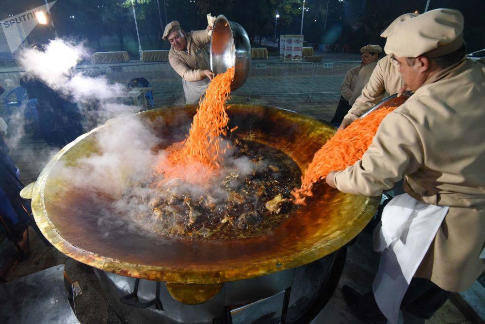 طهاة خلال اعداد أكبر طبق بيلاو (أو بيلاف) على طريقة دوشنبه ، خلال مهرجان  أوشي بالاف في حديقة فردافسيفي دوشنبه، طاجكستان
