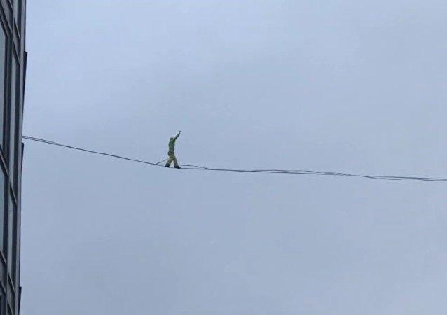 رجل يسير على حبل على ارتفاع شاهق ويقع (فيديو)