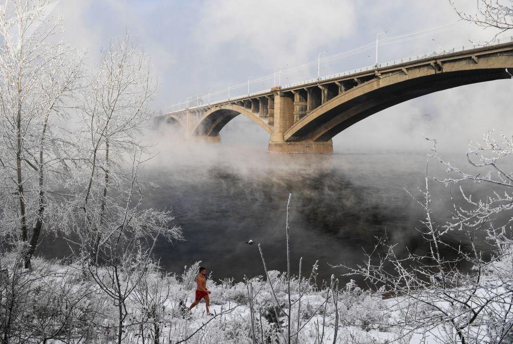أحد أعضاء نادي كريوفيل للسباحة الشتوية يسير عليى خلفية جسر كومونالني