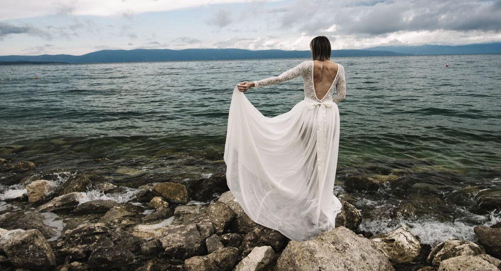 عروس في ثوب الزفاف قرب البحر
