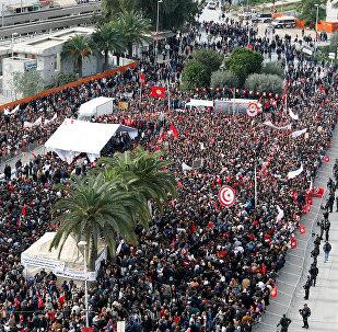 يحمل الناس أعلامًا وهم يحتجون على رفض الحكومة رفع الأجور في تونس العاصمة