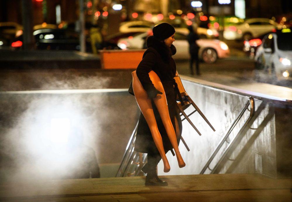 امرأة تحمل الجزء الأسفل من دمية بعد خروجها من ممر تحت الأرض في موسكو، 21 نوفمبر/ تشرين الثاني 2018