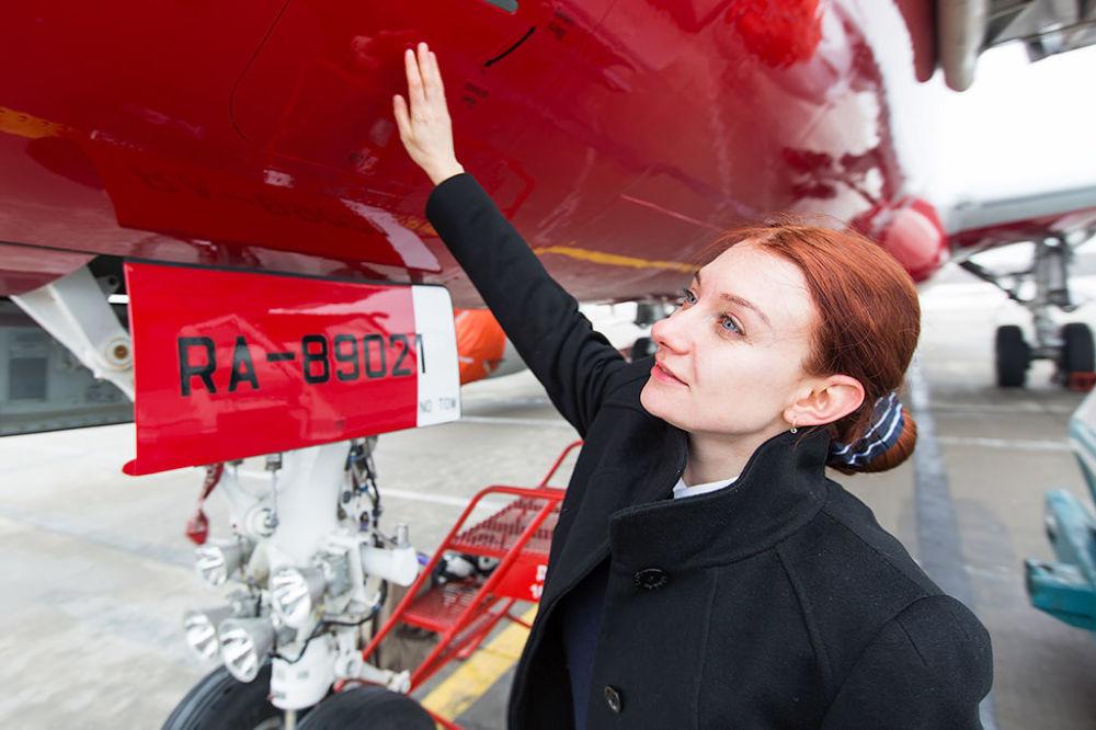 داريا سينيتشكينا، امرأة مساعد-طيار تتفقد طائرة سوخوي سوبرجيت 100 لشركة ريد وينغز الروسية