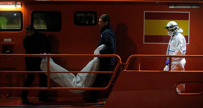 جثة مهاجرة في أثناء نقلها من قارب إنقاذ في ميناء ملقة