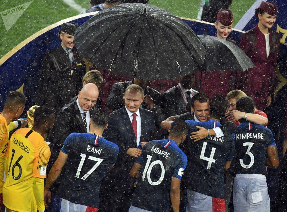 الرئيس الروسي فلاديمير بوتين والرئيس الفرنسي إيمانويل ماكرون ورئيسة كرواتيا كوليندا غرابار-كيتاروفيتش خلال مراسم توزيع جوائز بطولة فيفا لكأس العالم لكرة القدم روسيا 2018 في ملعب لوجنيكي بموسكو، 15 يوليو/ حزيران 2018