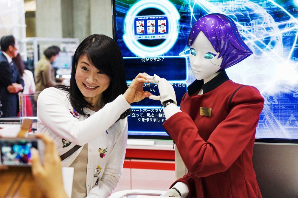 زائرة تتصور مع رجل آلي FASHION Junko Koshino في المعرض الدولي للروبوتات IREX  في طوكيو