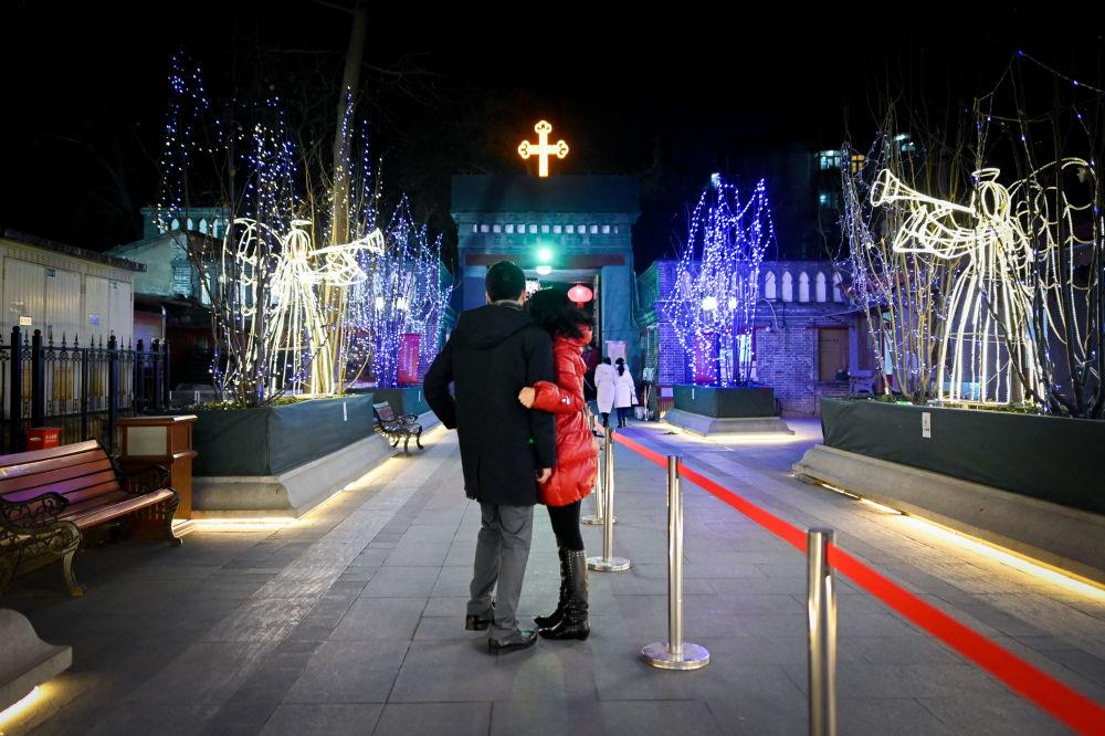 زوجان أمام الكنيسة الكاثوليكية قبل بدء قداس عيد الميلاد في بكين