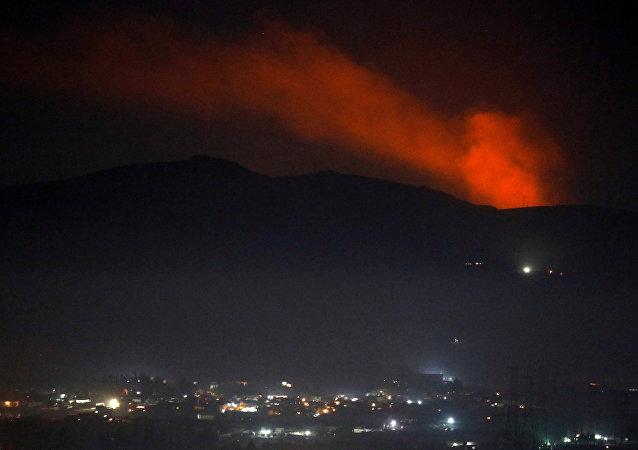 تصاعد الدخان وراء أحد الجبال المحيطة بدمشق بعد الغارات الإسرائيلية على مواقع للجيش السوري