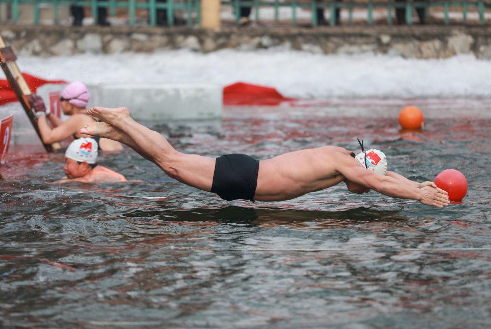 رجل خلال مسابقة للسباحة الشتوية عند درجة حرارة 21 درجة مئوية تحت الصفر بمقاطعة لياونينغ، شمال شرقي الصين