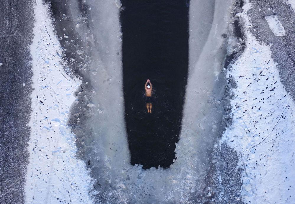 رجل يسبح في بحيرة متجمدة جزئيا في شنيانغ بمقاطعة لياونينغ