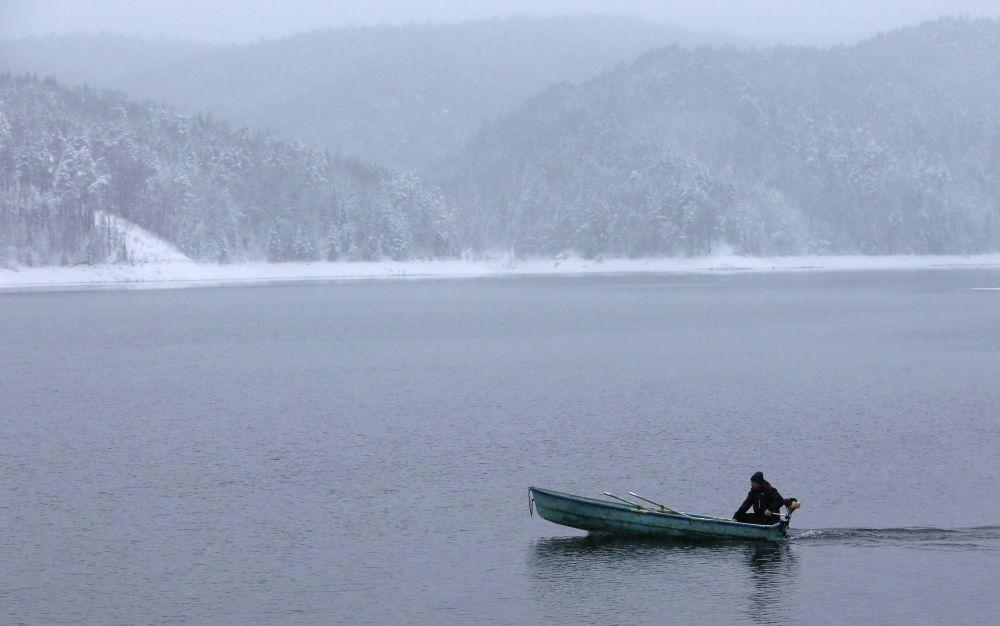 رجل يعبر نهر ينيسي بالقرب من مدينة كراسنويارسك الروسية