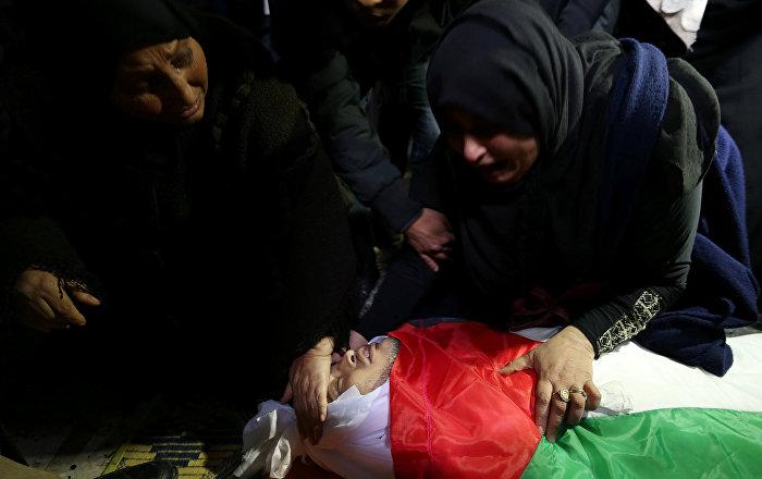 إحدى أقارب كرم فياض وهي تنظر إلى جثمانه خلال جنازته في جنوب قطاع غزة