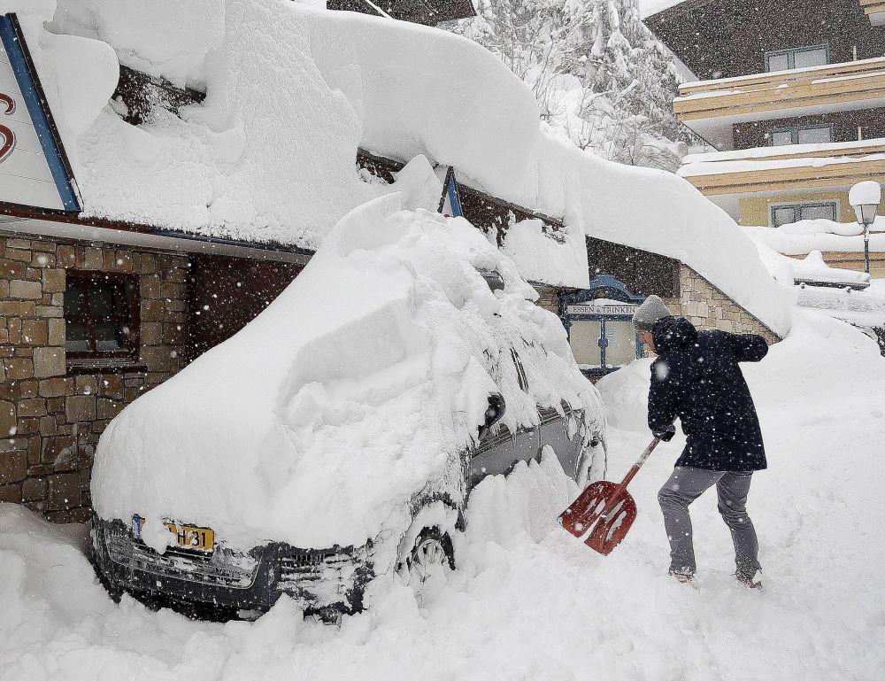 سائح يحاول تنظيف واخراج سيارته العالقة في الثلج في فيلزموس، النمسا 5 يناير/ كانون الثاني 2019